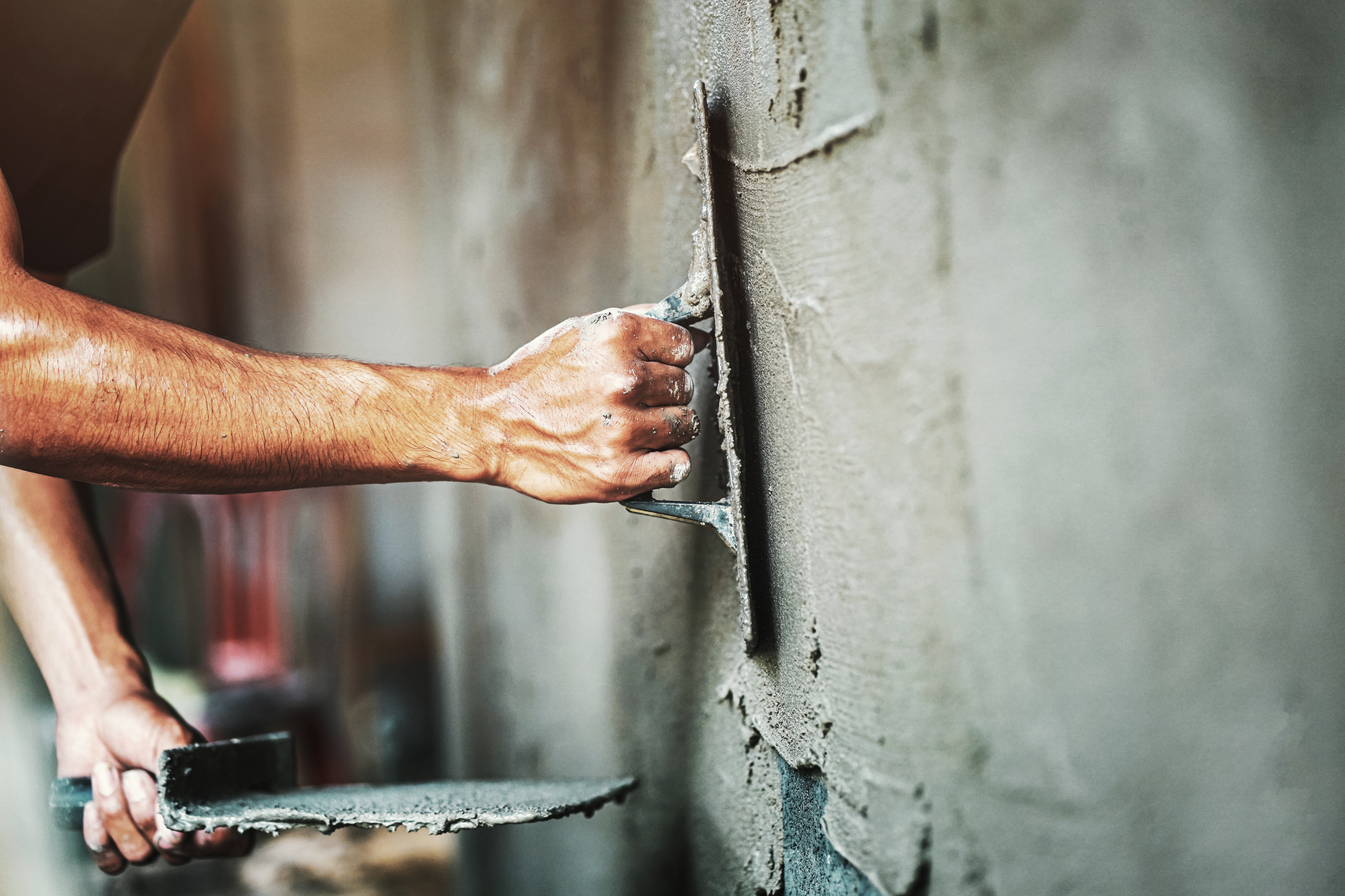 closeup hand of worker plastering cement
