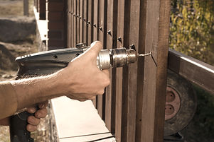 Man%20hands%20drilling%20wooden%20fence%20to%20metal%20construction.%20Building%20a%20wooden%20fence