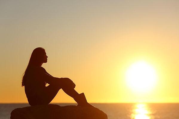 Teen Girl Looking At Sunrise Across Ocea