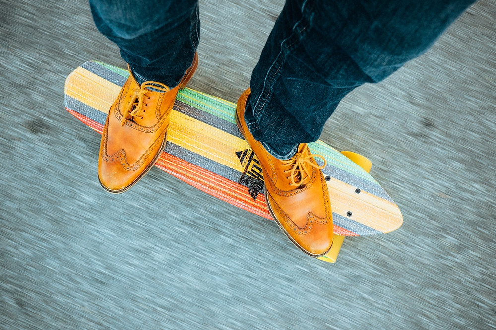 overhead view of skateboard and person in dress shoes riding it
