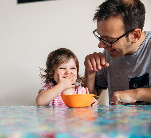 Dady and young kid eating breakfast together