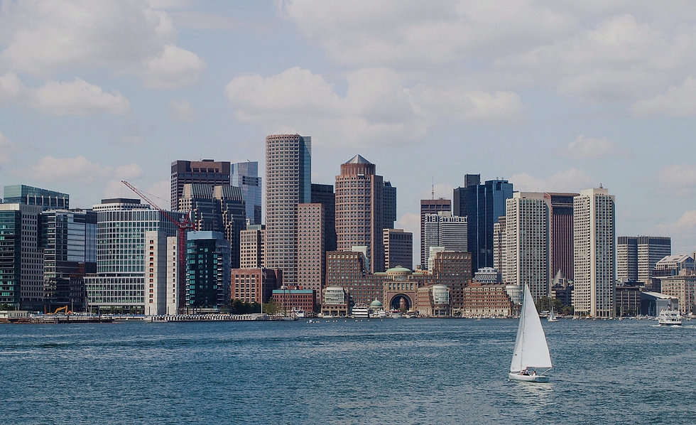 Sailboat on water with city backdrop