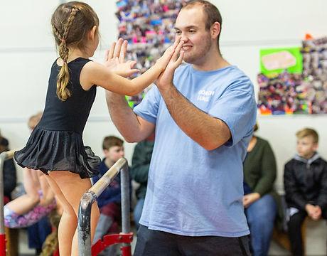 Coach teaching preschool gymnast on bars