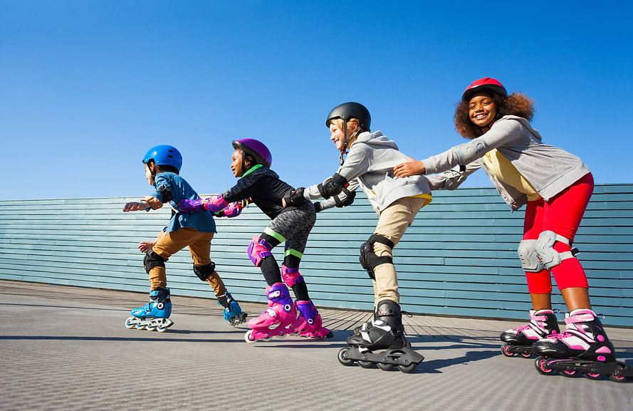 Kids in safety helmets rollerblading on