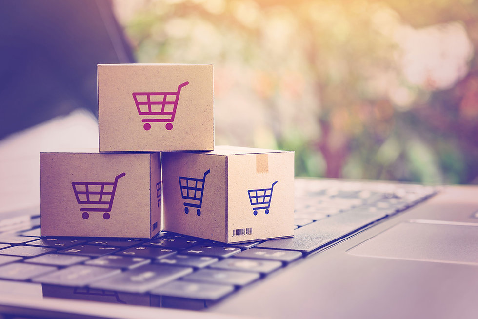 Three small boxes with shopping cart pictures on them sitting on top of a keyboard. Shop online stor