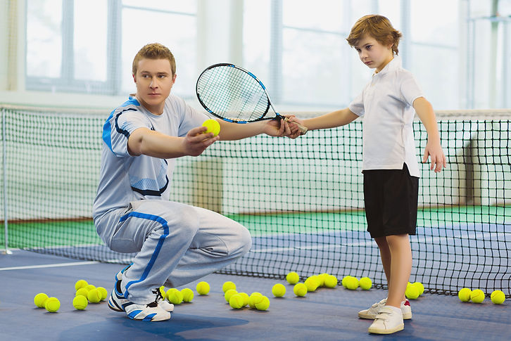 Tennis flooring used for outdoor multipurpose flooring. A man and his son playing tennis