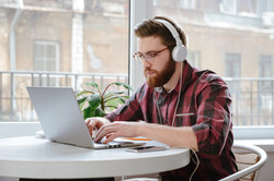 Image of concentrated bearded young man student sitting in cafe while using laptop computer and list