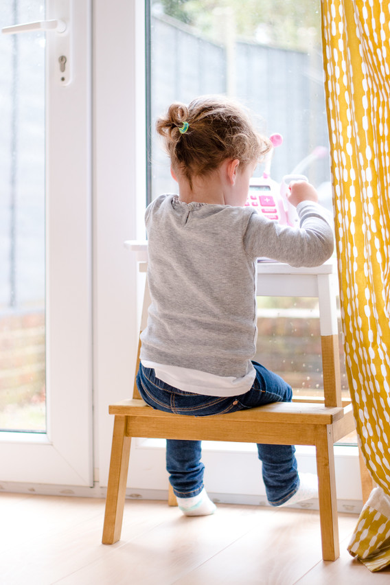 little girl plays alone, sat on on stool by patio door Stephanie Atkins Photography