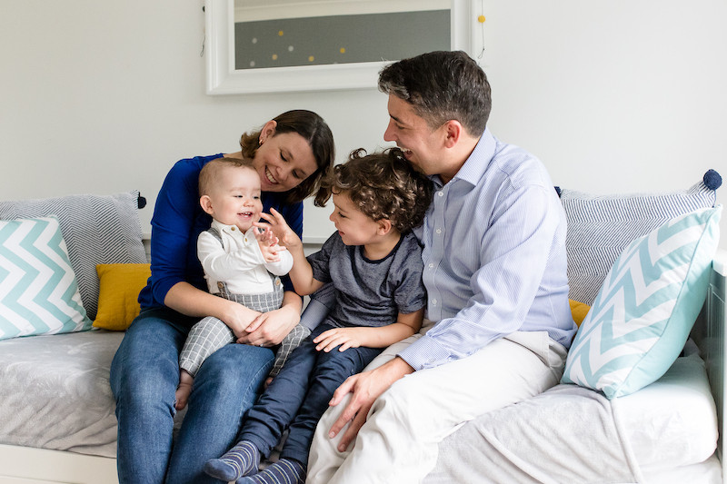 family of four, huddle and laugh together on bed.  Stephanie Atkins Photography
