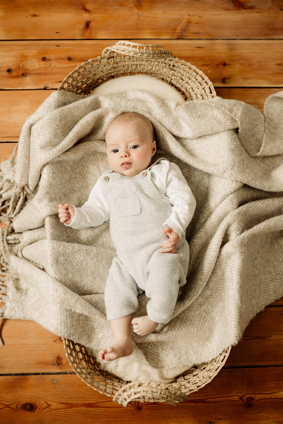 baby boy laying in moses basket