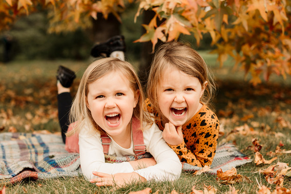 sisters lying on a blanket in autumn