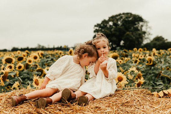 twin girls sitting on a hay bale in the sunflowers