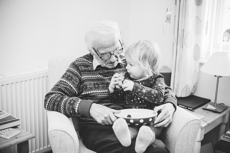little girl shares snack with grea grandfather sat on his knee. Stephanie Atkins Photography