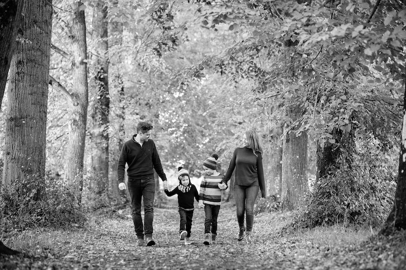 black and white image of family of 4 wlaking througha path of trees.stephanie atkins photography