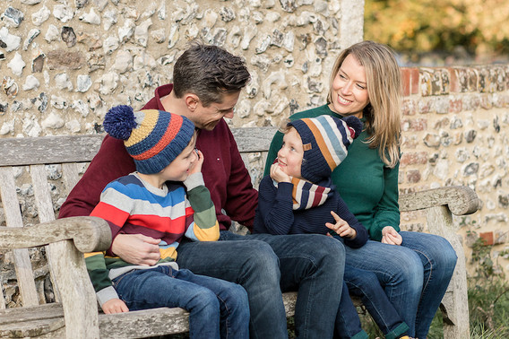 family of 4, 2 boys sit on bench in the autumn smiling at each other- stephanie atkins photography