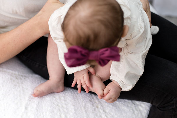 baby girl touching her toes with burgandy bow hedband Stephanie Atkins photography