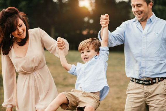 family swinging son between their arms
