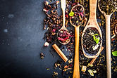 Virious kinds of tea in wooden spoons on