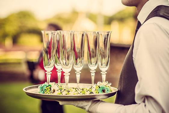 Empregado de mesa com flautas de Champag