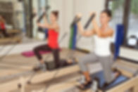 Two girls are exercising pilates using p