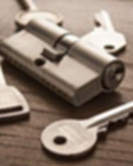 door lock with keys on wooden surface