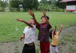 children jumping for bubbles
