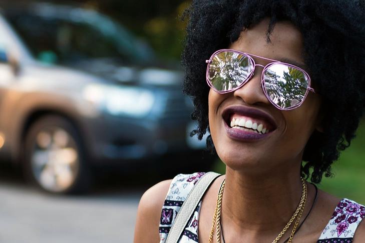 Black woman in sunglasses smiling