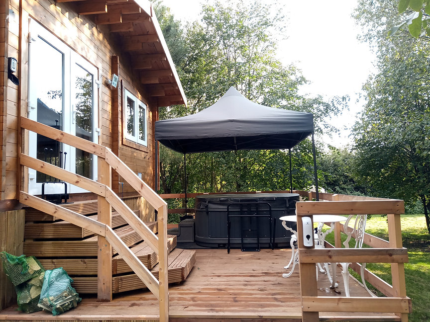 Swan Lodge at Hawthorn Hideaway, a log cabin for 2 with a private covered hot tub on your decking and seating for 2.