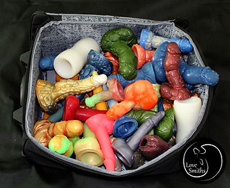 A hand luggage full with colourful dildos and masturbators from Love Smiths