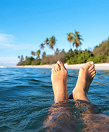 Feet floating in the ocean with beach and palm trees in the distance