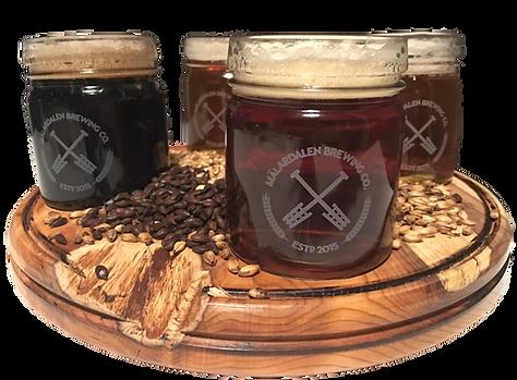 Fyra glas med öl som står på en träbricka.