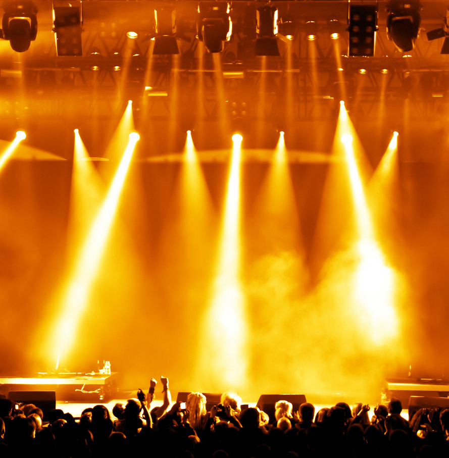 A concert scene of a crowd standing in front of a stage with blinding red lights illuminating the image.