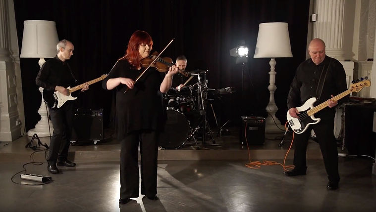 A 4-piece band of fiddle, guitars and drums playing in a formal room