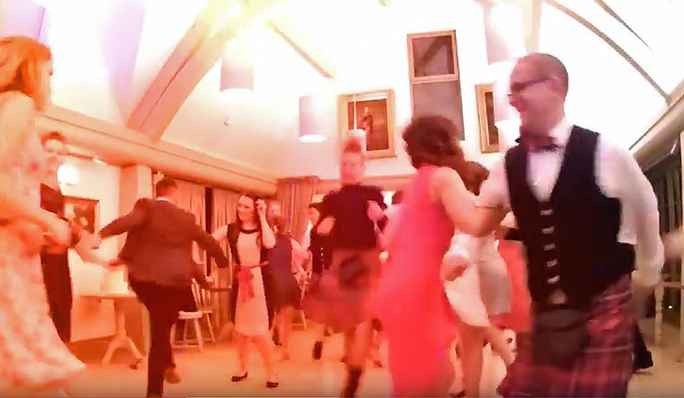 Women and kilted men dancing in a ceilidh