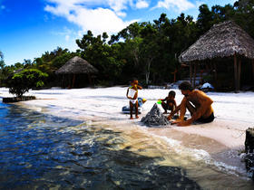 Viktor on the lake beach constructing a sand pyramid with Ray and Nic
