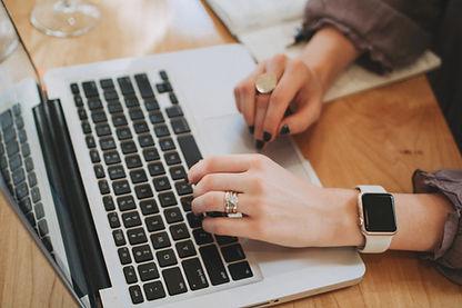 Twee handen typen op laptop