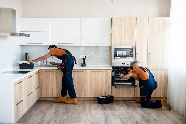 Two handymen, workers in uniform fixing, installing furniture and equipment in the kitchen