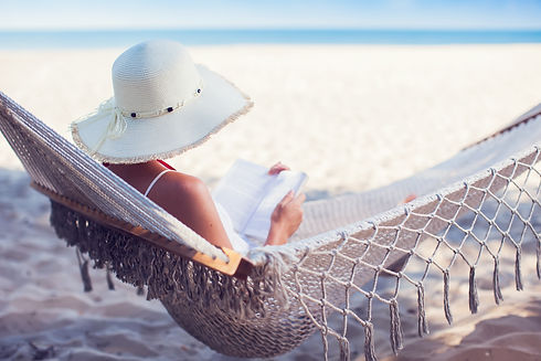 Young lady reading a book in hammock on