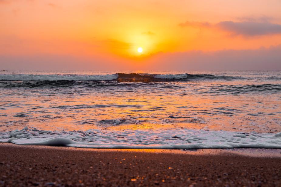 sunrise-over-wavy-ocean-on-sandy-beach.j