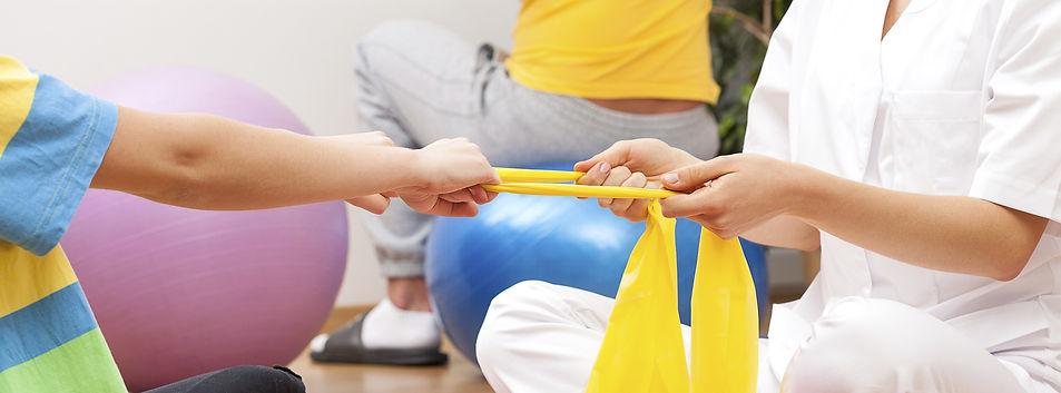 Exercício realizado por um paciente com seu fisioterapeuta com um elástico amarelo.