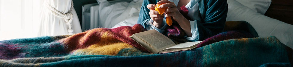 woman reading wrapped in avoca throw
