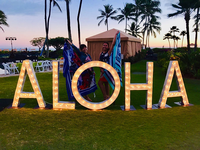 two women standing behind aloha sign