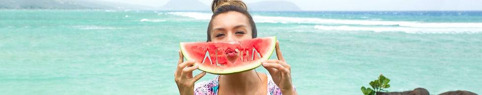 woman holding half a watermelon