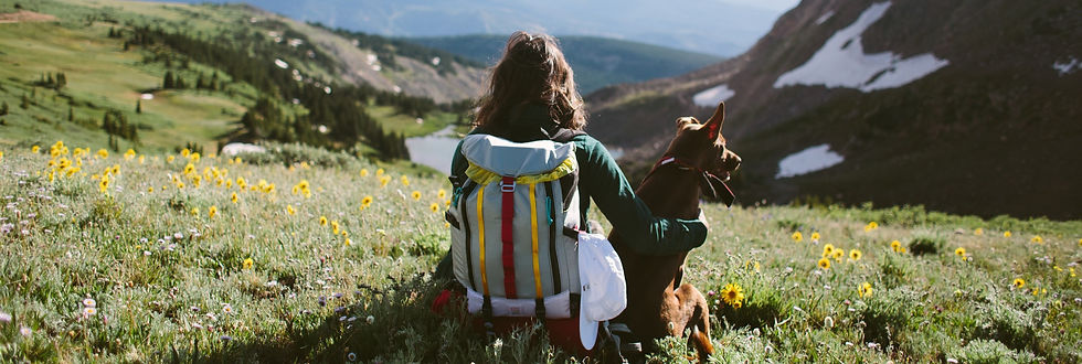 woman wearing topo bag sitting with dog
