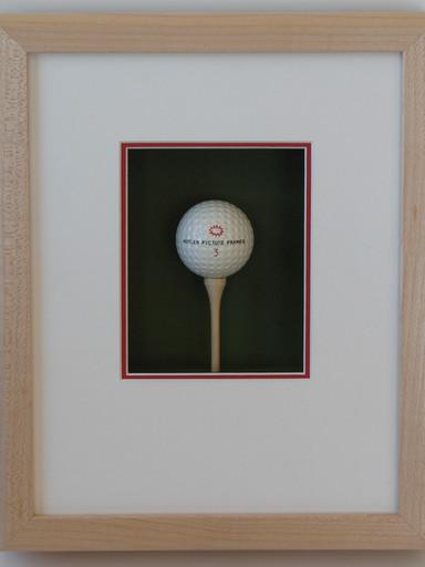 Framed golf ball on tee in shadowbox