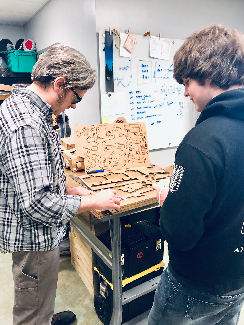 Matthew Craig (VW eLab specialist) and Kaleb Hale (freshman) analyze construction of the pinball playboard.