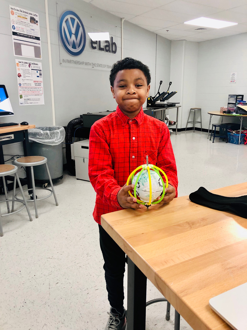 Samuel Byron poses with his globe project.