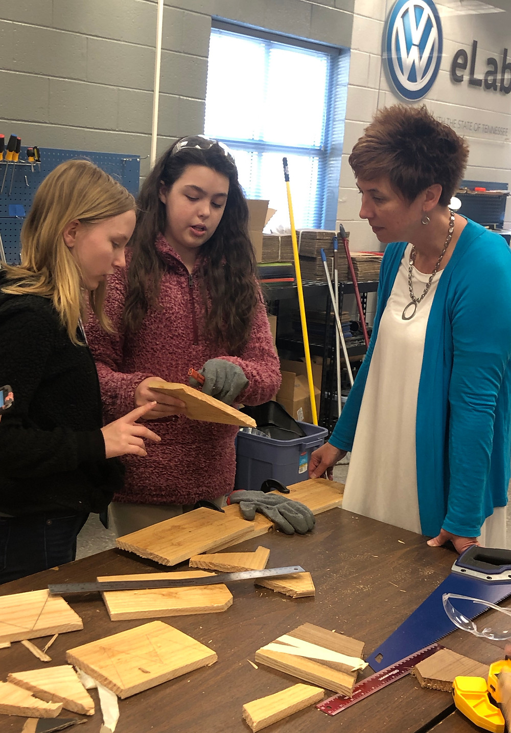 Seventh grade students review their project's progress with Smith.
