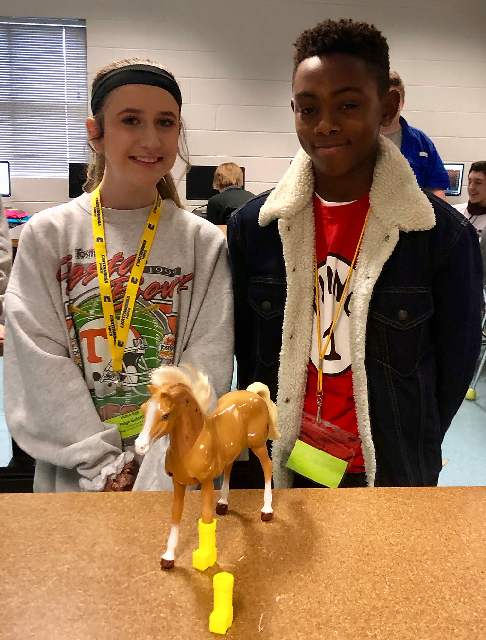 Paige Goforth & Nicholas Short pictured with two iterations of the horse prosthetic they created with the 3D printing machine