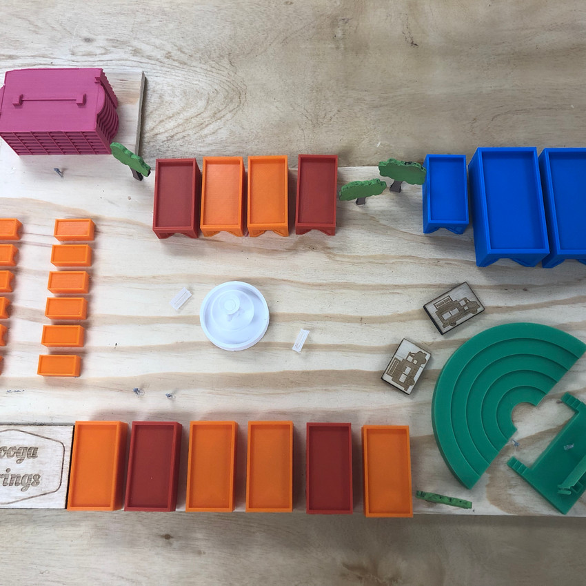 Materials:  Logo & food trucks -  laser printed on wood Trees - Laser cut and hand painted / sanded  Buildings - 3D printed  Color codes:  Orange - shopping  Red - food Blue & green - entertainment Fushia - parking garage White - fountain & benches